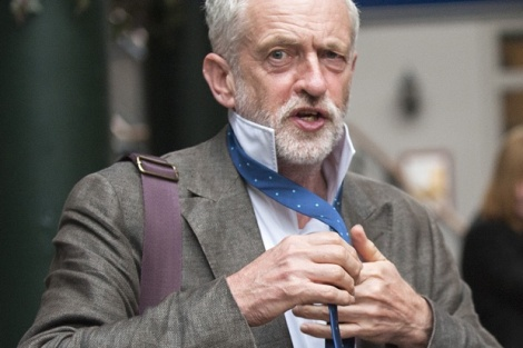 British Labour party leadership contender Jeremy Corbyn poses for pictures with a tie that he was given by a charity worker as he arrives to address a public rally in Glasgow, Scotland, on August 14, 2015. Voting began Friday to elect the new leader of Britain's main opposition Labour party, with Jeremy Corbyn, a veteran socialist who would move the party significantly to the left, favourite to win. AFP PHOTO / LESLEY MARTIN (Photo credit should read LESLEY MARTIN/AFP/Getty Images)